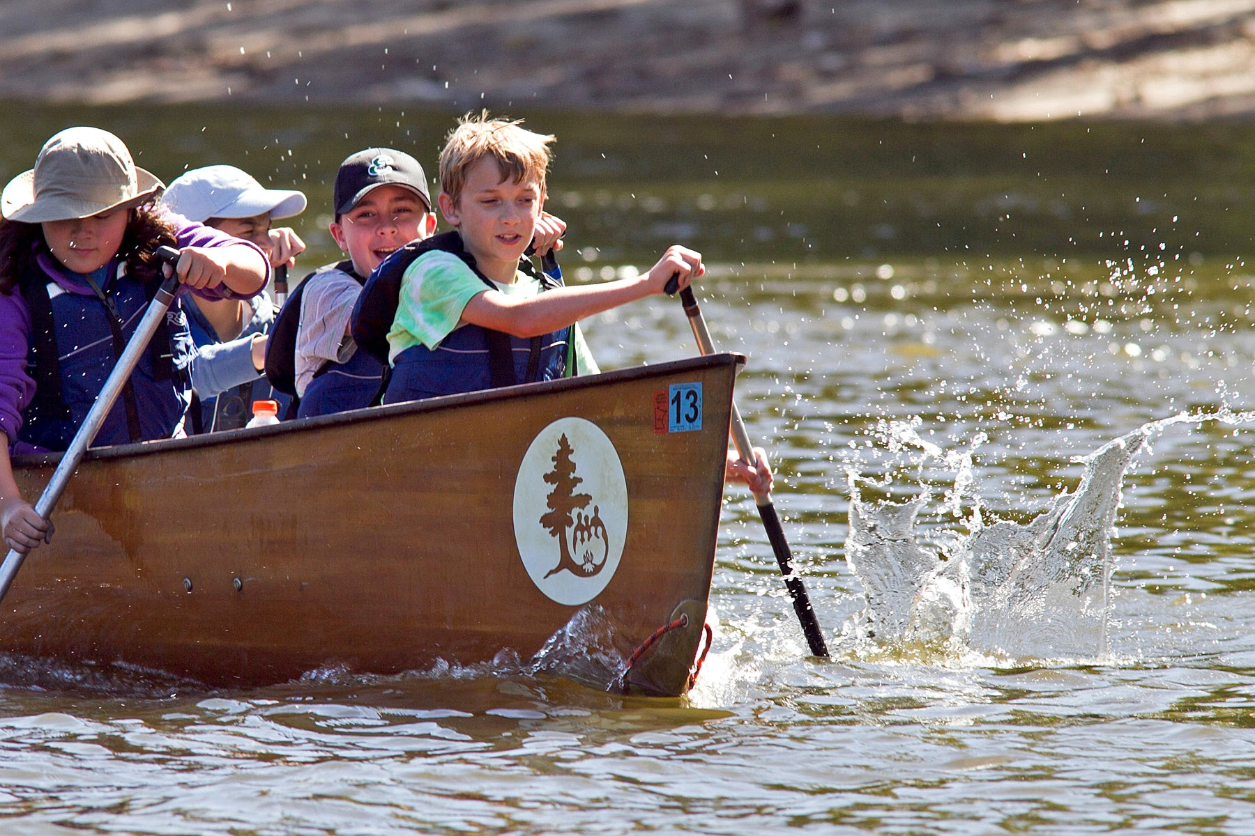 Four participants in the bow of a Voyageur canoe paddle together, making the water splash.