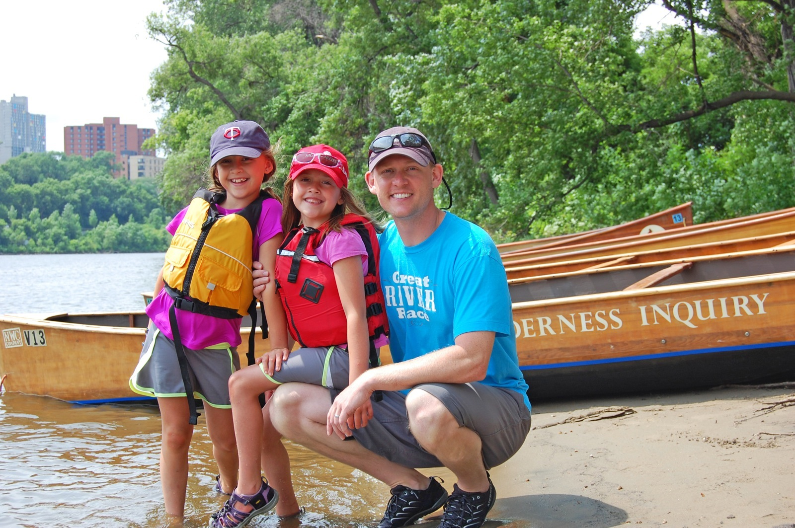 A smiling father and two daughters pose on the beach in front of a group of Voyageur canoes.