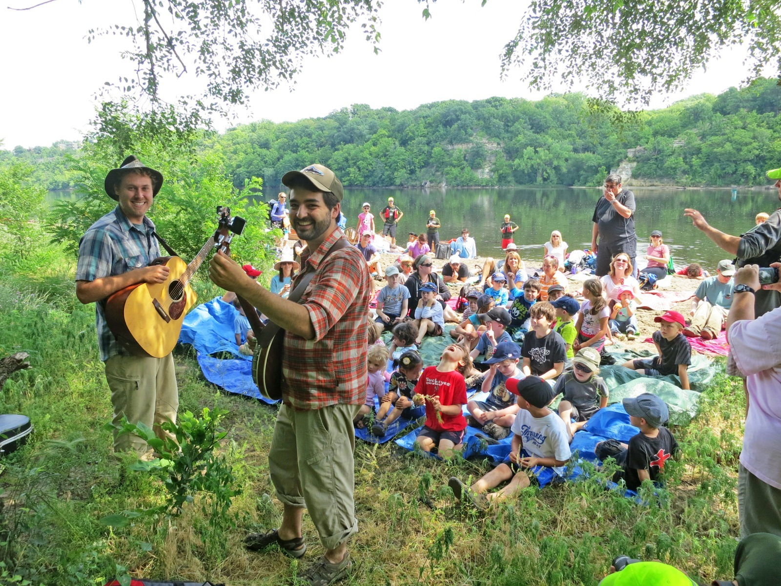 Two musicians from the Okee Dokee Brothers entertain a crowd of people sitting on the banks of the Mississippi River.