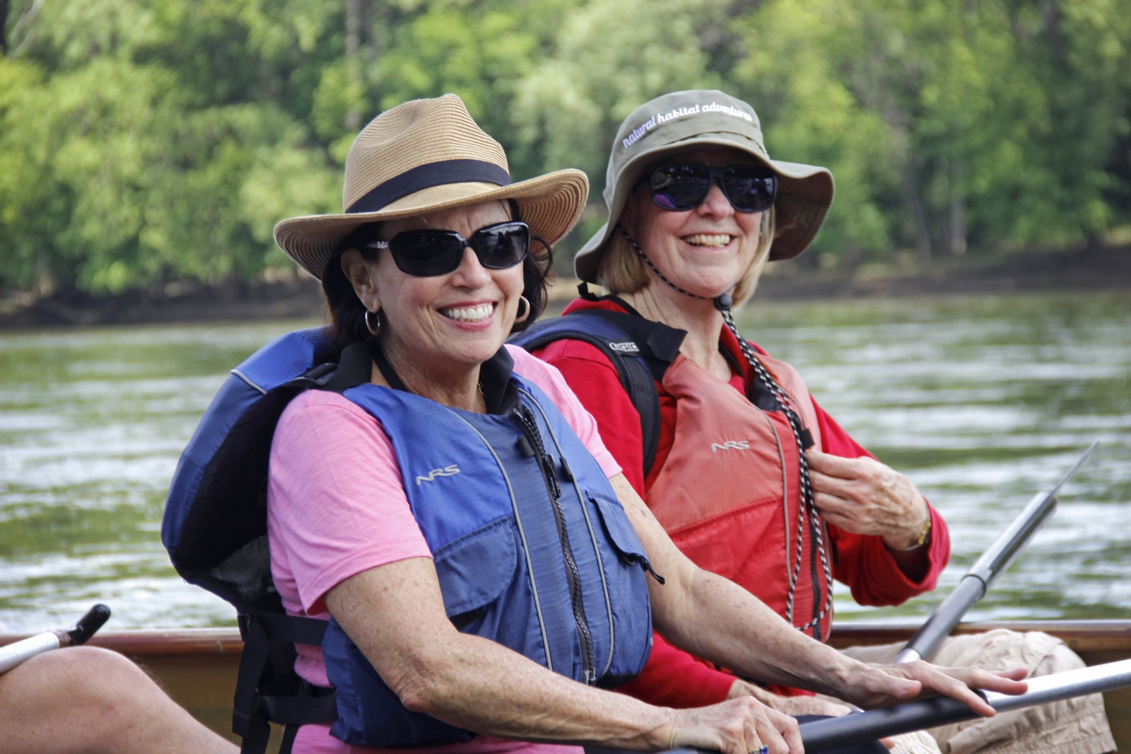 Two older women sit side-by-side in a Voyageur canoe.