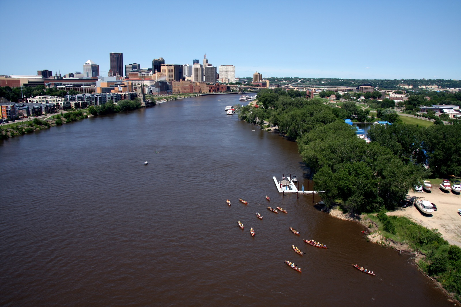 A fleet of voyageur canoes makes a proud site on the open river with the city of Saint Paul in the background.