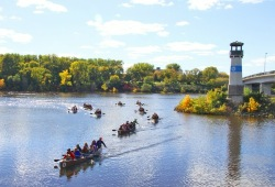 Nine Voyageur canoes paddle towards the camera, with bright green trees and a small lighthouse in the background.