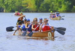 A group of paddlers in a Voyageur canoe smile for the camera.