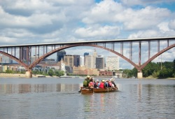 A Voyageur canoe makes its way towards the arch of the High Bridge with St. Paul in the background.