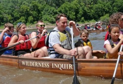Close-up of a group of adults and kids practicing their paddle strokes in a Voyageur canoe.