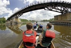 A group of paddlers in a Voyageur canoe pass under a bridge on the Mississippi River.