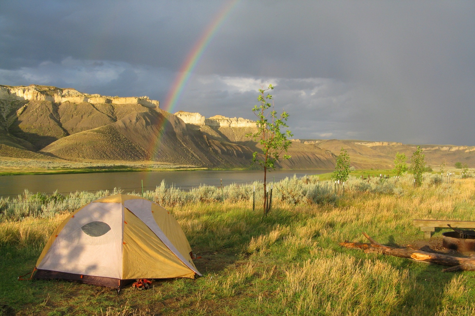 Under gray skies, a rainbow arches over the Missouri River and our campsite near Slaughter River.