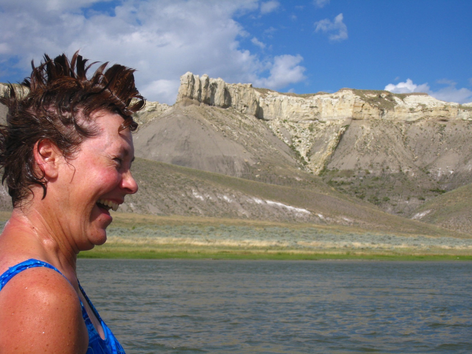After a swim, a woman sports a mohawk that resembles the Missouri River cliffs in the background.