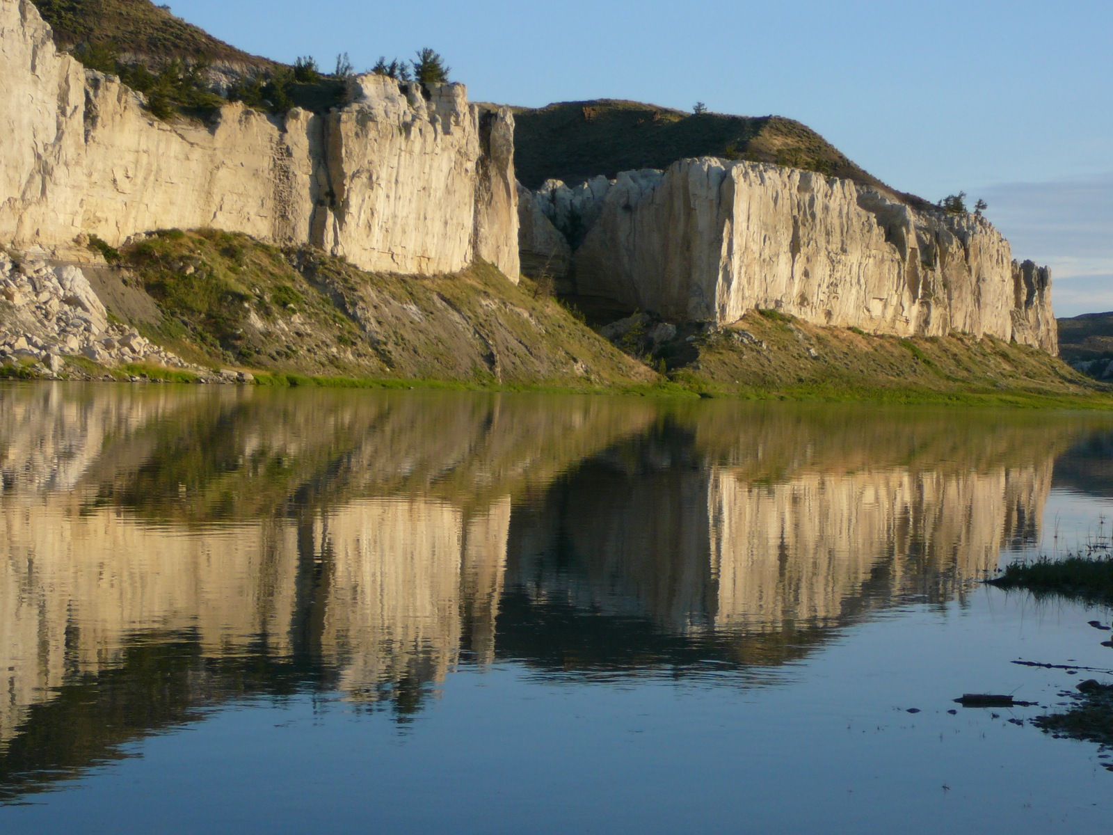 Rock faces on the Missouri River are reflected in the glassy water of the river.