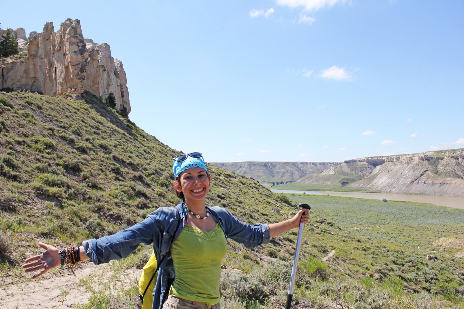 A woman smiles for the camera while on land with the Missouri River and rock formations in the background.