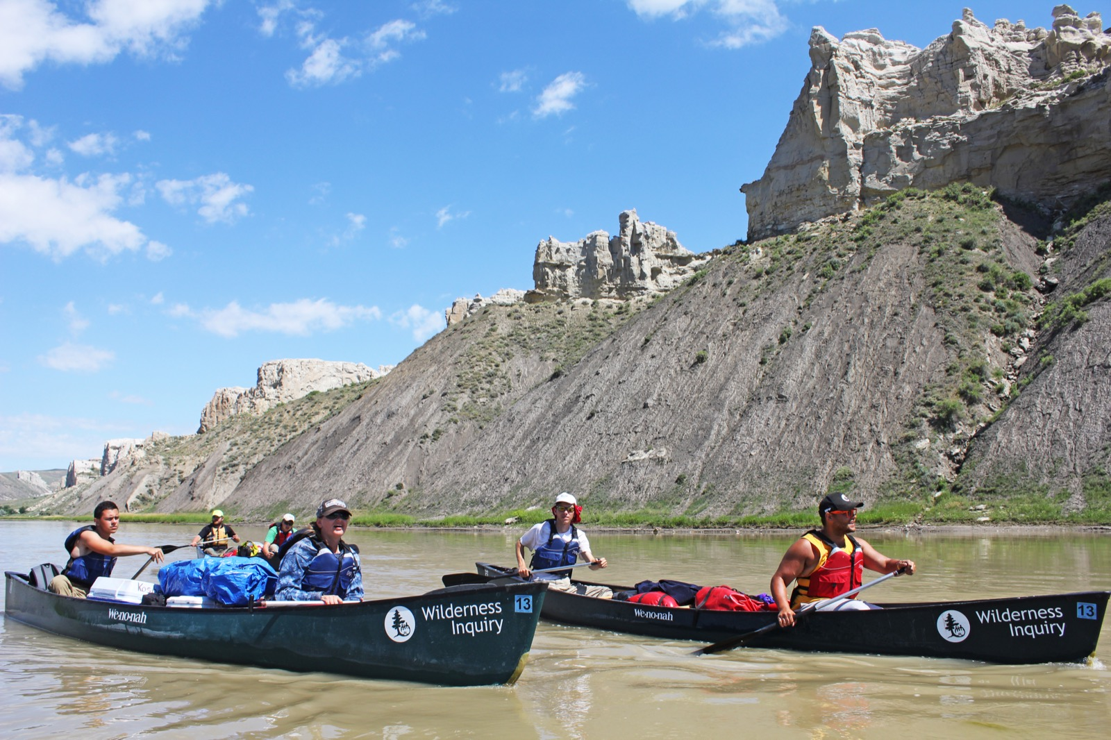 Participants in three dark green tandem canoes enjoy a sunny day of paddling below the Missouri River's towering canyon walls.