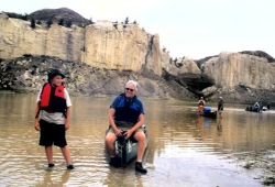 Participants walk their canoes through shallow waters on the Missouri River with steep white cliffs in the background.