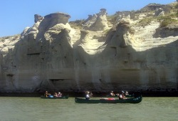 Three Wilderness Inquiry tandem canoes paddle past the White Cliffs on the Missouri River.