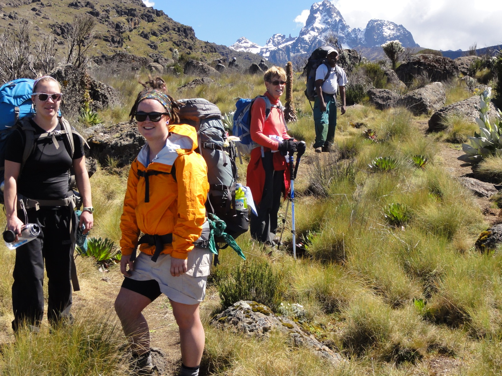 A group wearing backpacks takes a break along the trail; snow capped mountains in the background.