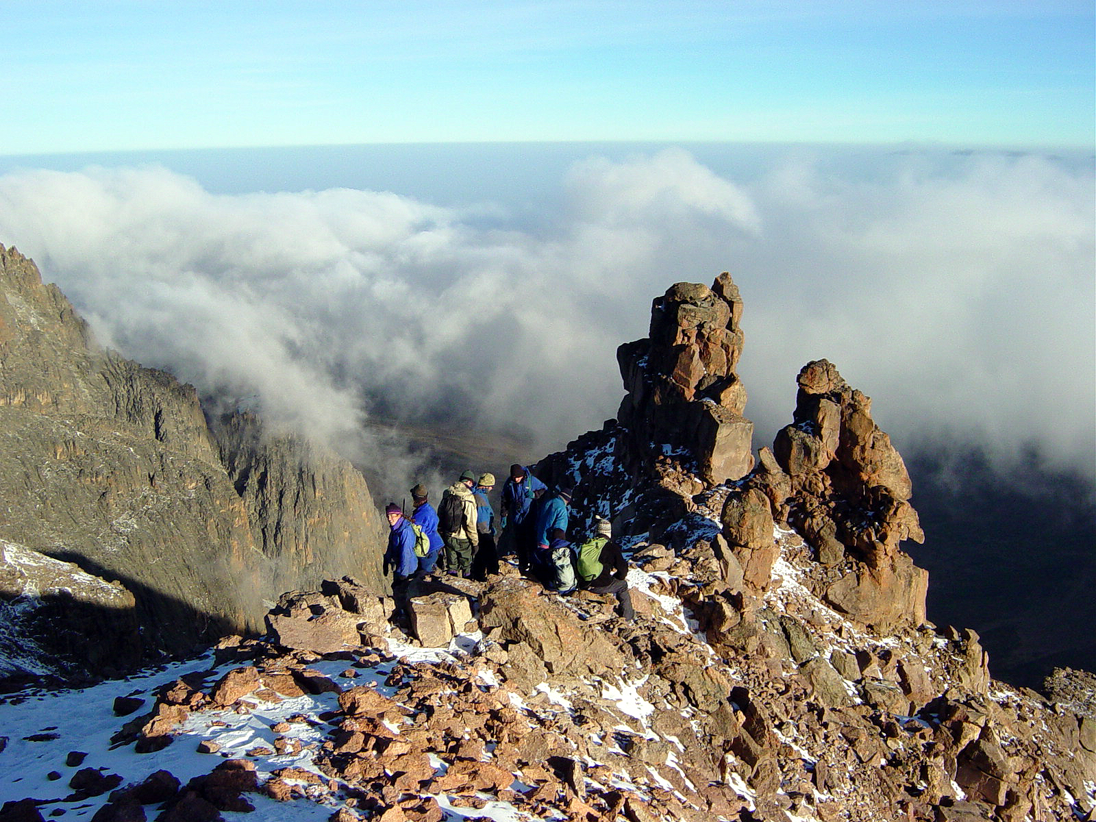 A group takes a break atop a rocky outcropping surrounded by wispy clouds at an altitude of 16,000 feet.