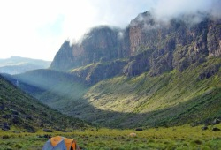 The sun breaks over the clouded canyon walls in a valley near Mt. Kenya.