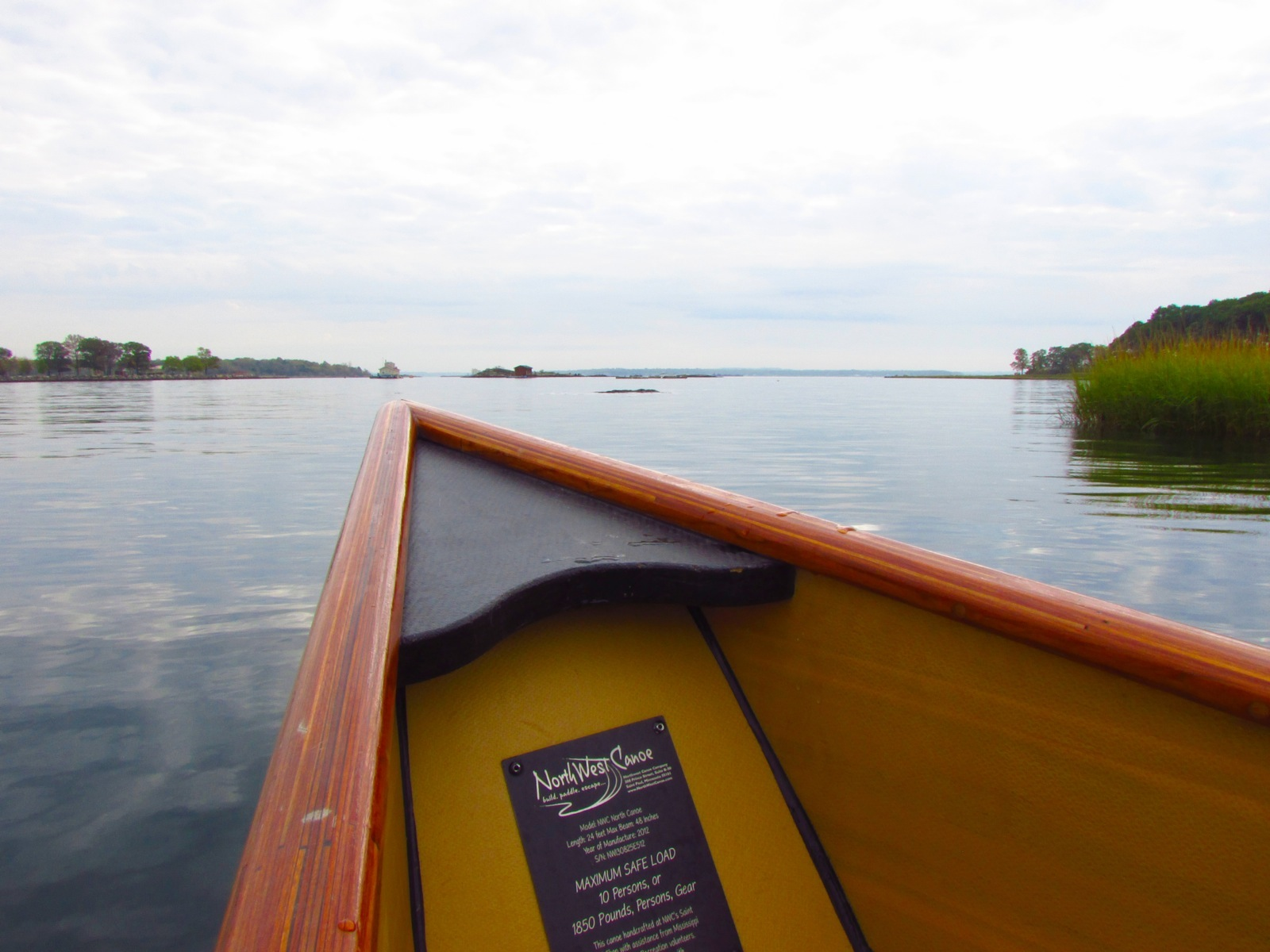 a photo of the bow of the canoe on a calm river on a sunny day