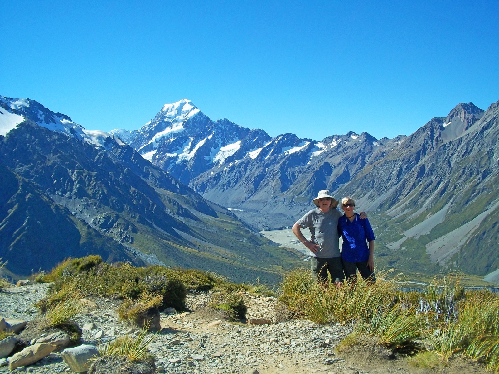 Two participants pose in front of mountains while hiking Sealy Tarns New Zealand