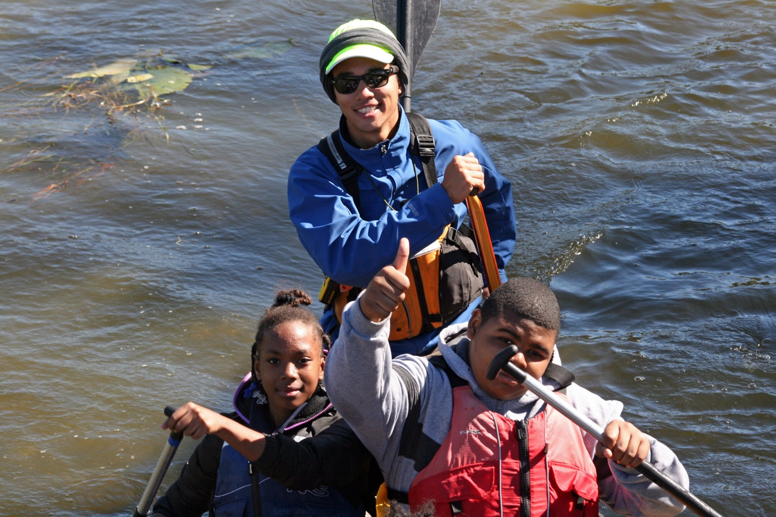 a member of staff and two participants smile for camera while paddling
