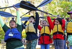 a staff member and kids reach their paddles above their heads while smiling