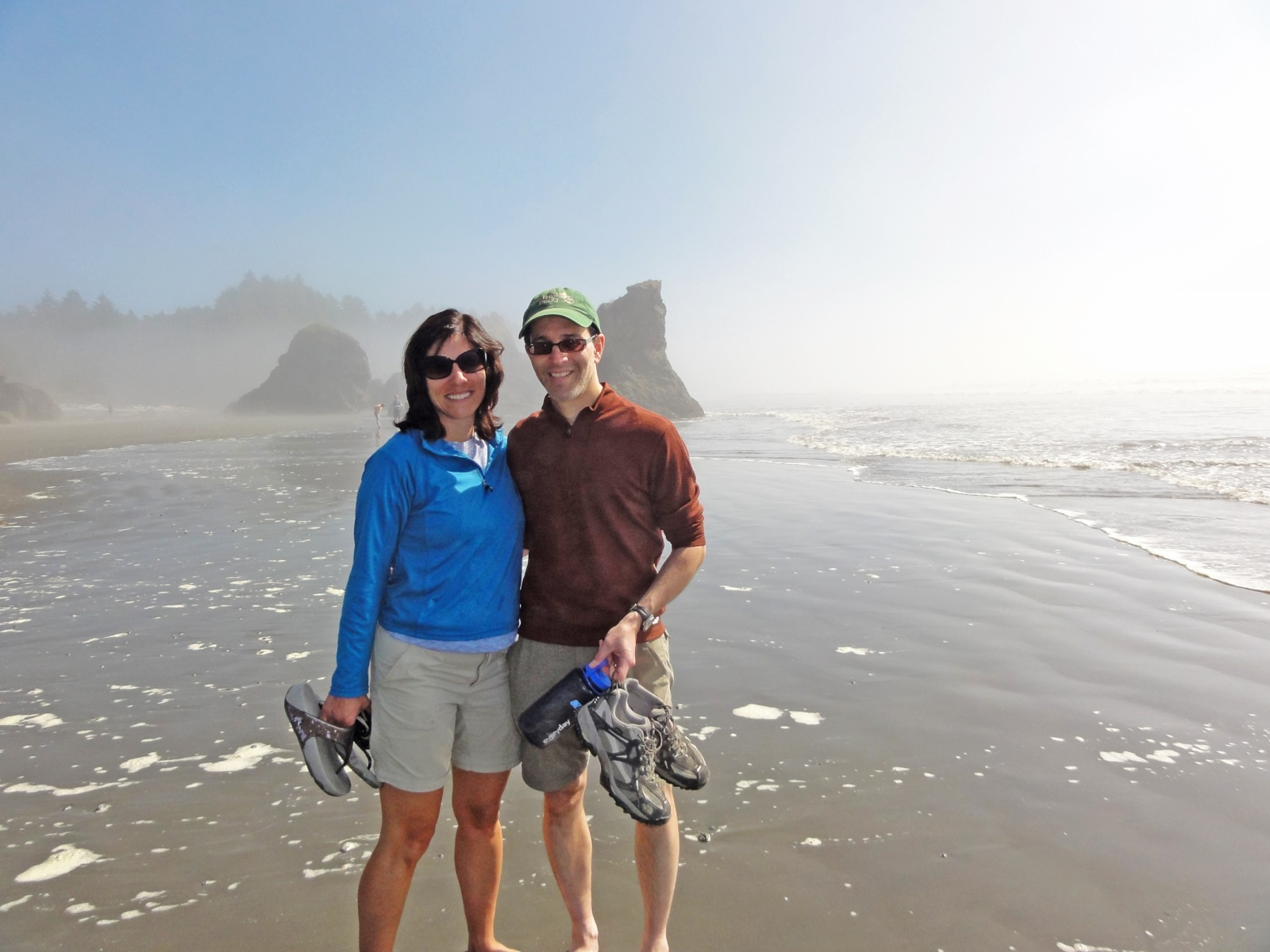 Lee and Amy Friedman carry their shoes and go barefoot on the misty beach of the Pacific Coast.