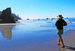 A participant walks along the beach, during a low tide, towards large rocks called sea stacks that jut up from the sand.