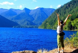 With her back to the camera, a participant opens her arms to blue waters and large, tree-covered mountains in front of her.