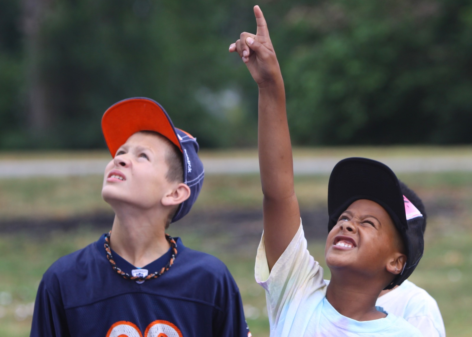 two young boys pointing up to the sky looking at wildlife