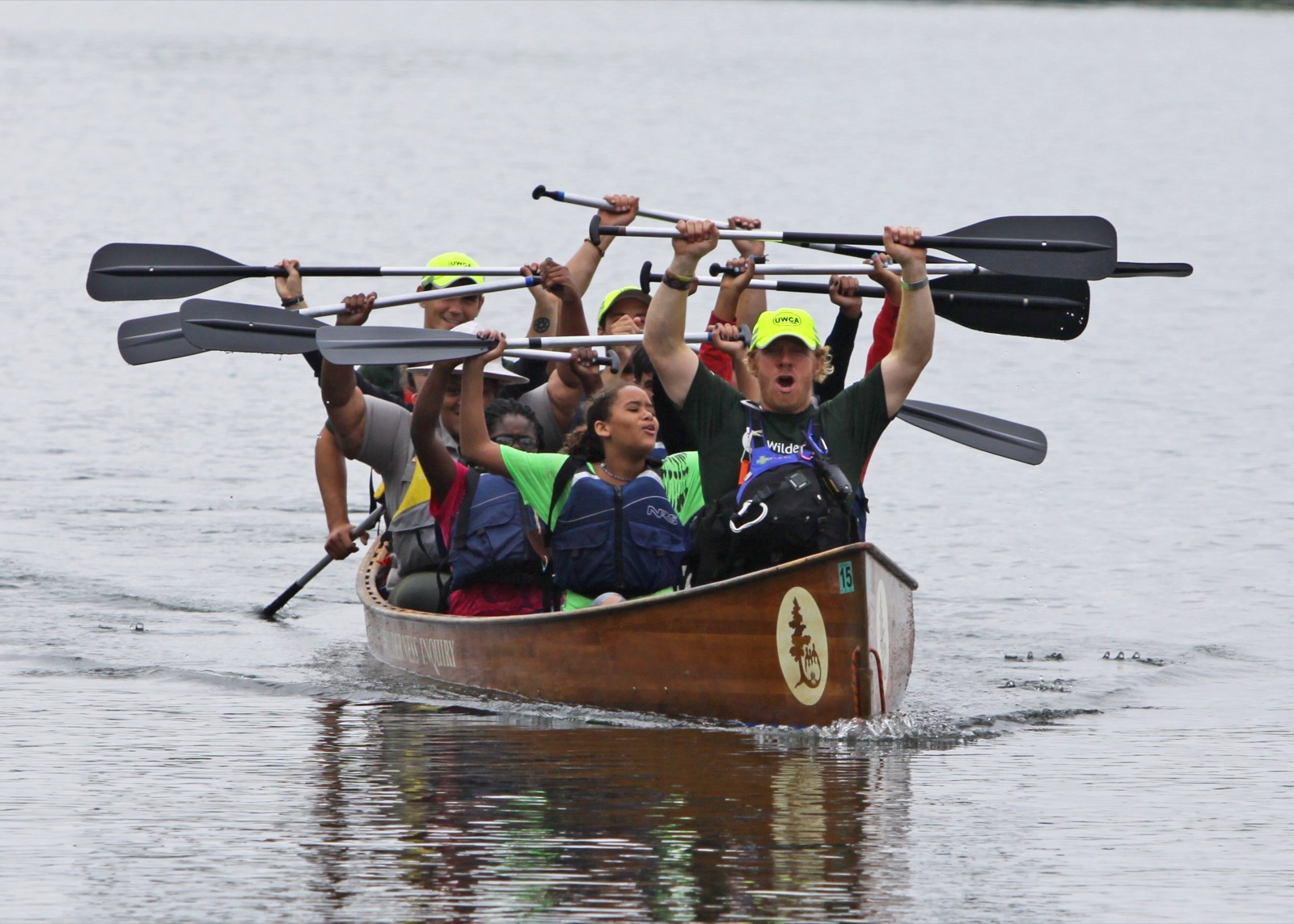 a group of canoemobile participants raise their paddles above their heads in their canoe