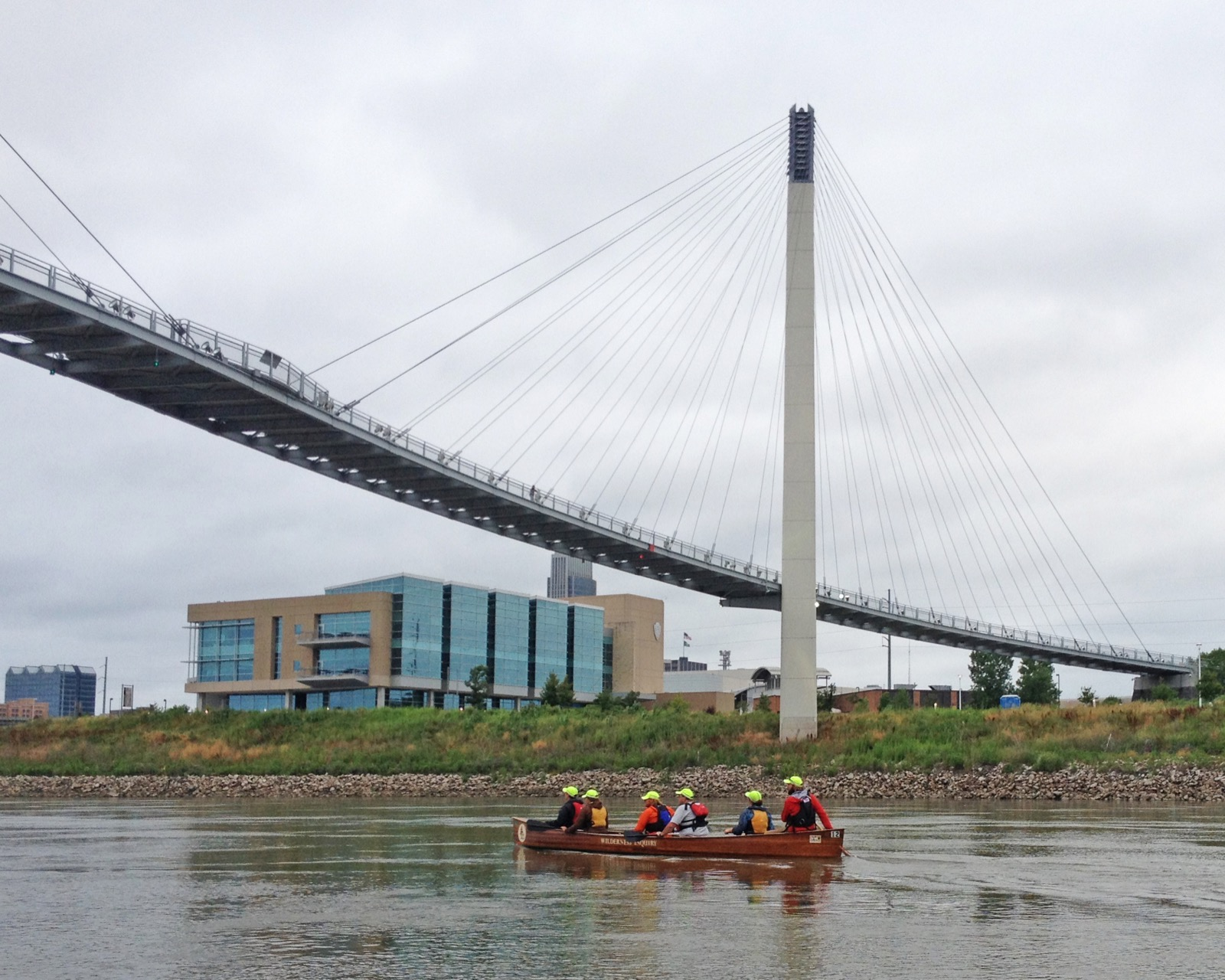 a group canoes underneath a large bridge in Omaha