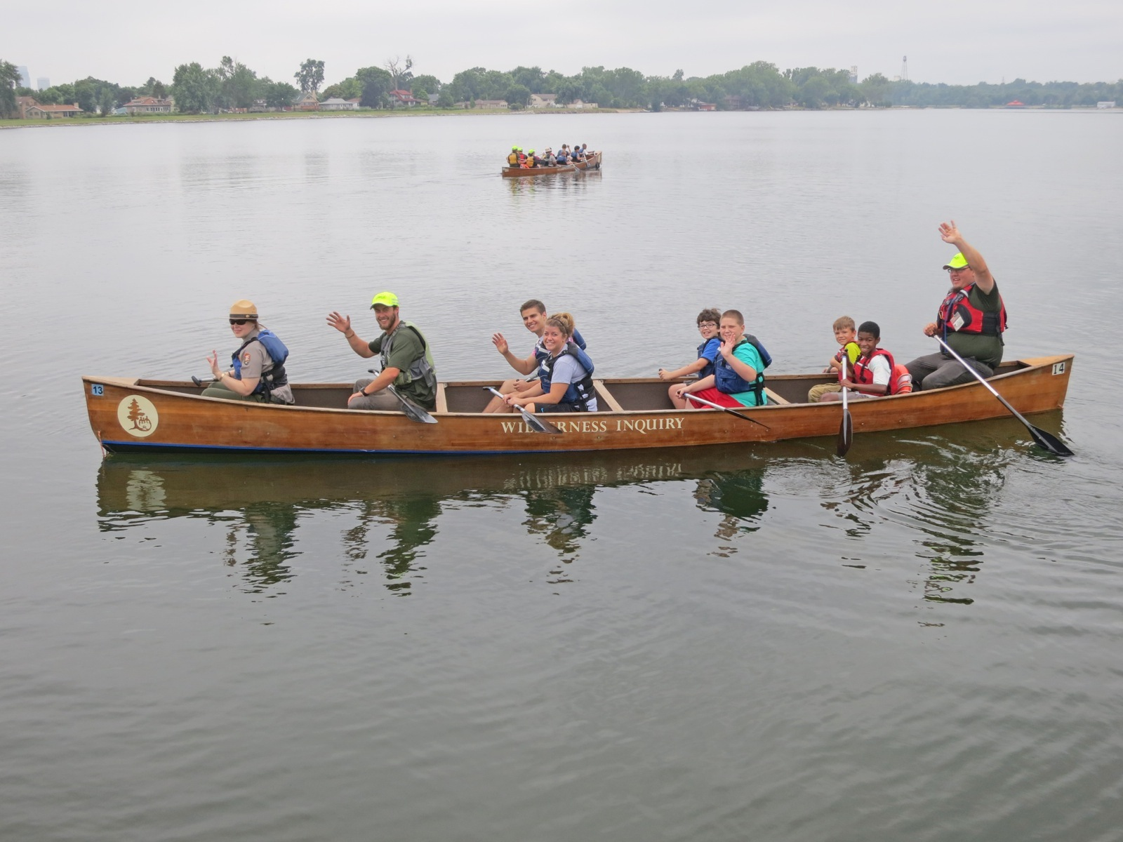 Canoemobile participants wave to camera while taking a break from paddling the canoe in Omaha