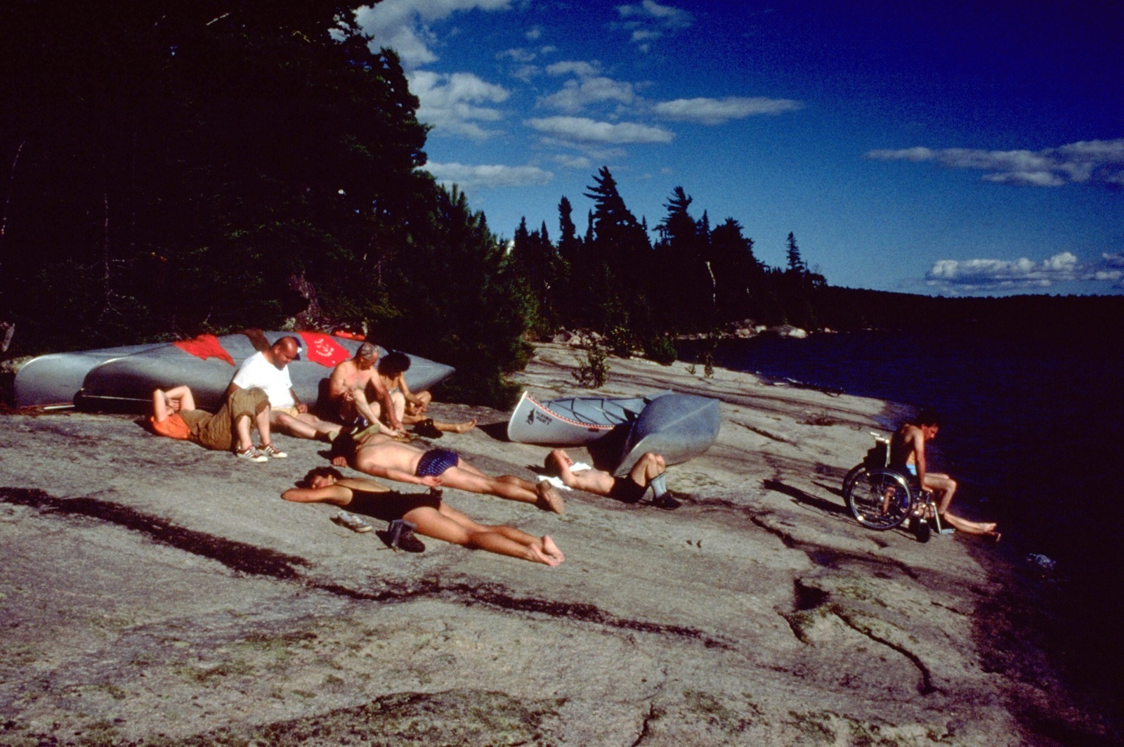 Participants sunbathe on a rock ledge next to their canoes in Ontario's White Otter Wilderness.