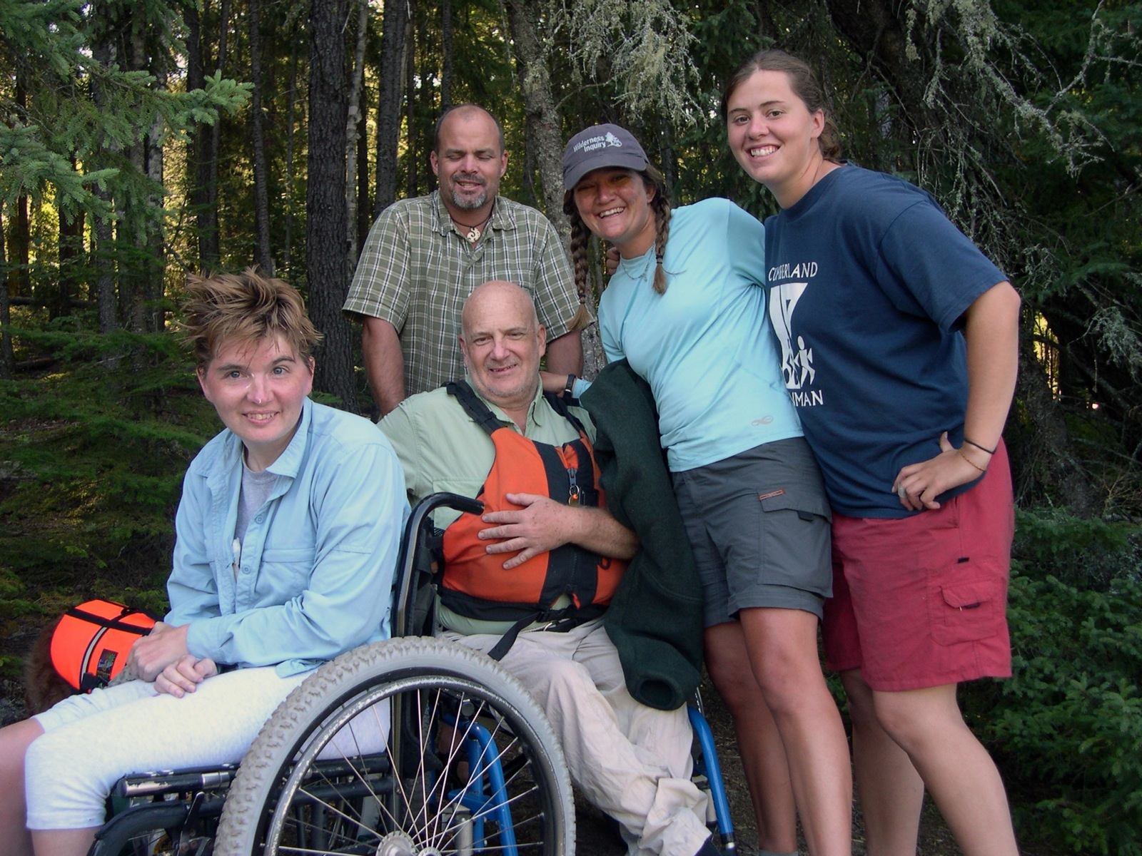 Five group members pose for a photo on the edge of the forest in the White Otter Wilderness.