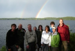 The group poses for a photo on the shore of Dashwa Lake in front of a double rainbow.