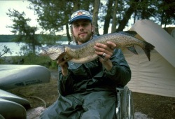 Jay, a participant who uses a wheelchair, shows off his large northern pike at camp near Dashwa Lake.