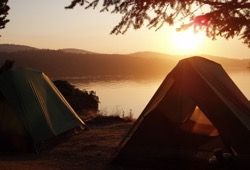 Tents set up on the shore of Dashwa Lake in the White Otter Wilderness at sunrise.