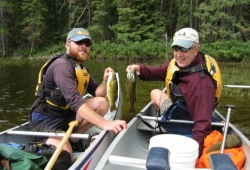 Two men in the bows of two canoes show off their fish in the White Otter Wilderness.