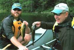 Two men in the bows of canoes hold up their recently caught fish to compare size.