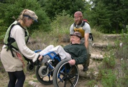 Two participants help a participant who uses a wheelchair over a portage in Ontario's canoe country.