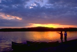 Two participants stand on the beach admiring the yellow, orange, and blue sunset next to two canoes