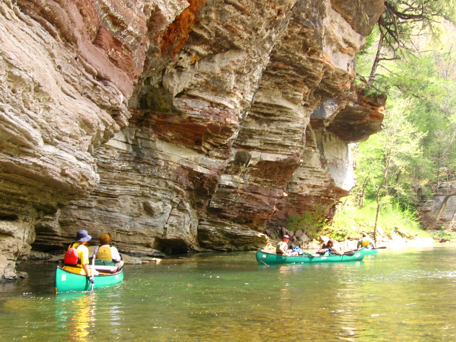 Two canoes paddle past tan and red overhanging cliffs near the Hasty campsite.