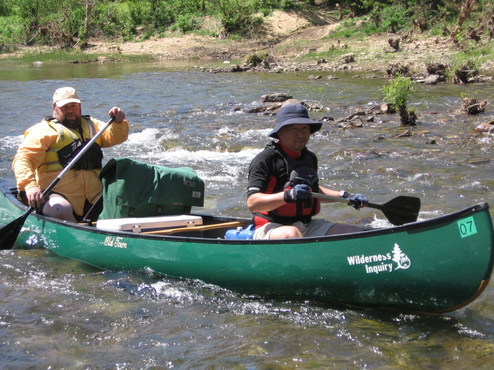 Two participants in a green tandem Wilderness Inquiry canoe maneuver a small section of whitewater in the Ozarks.