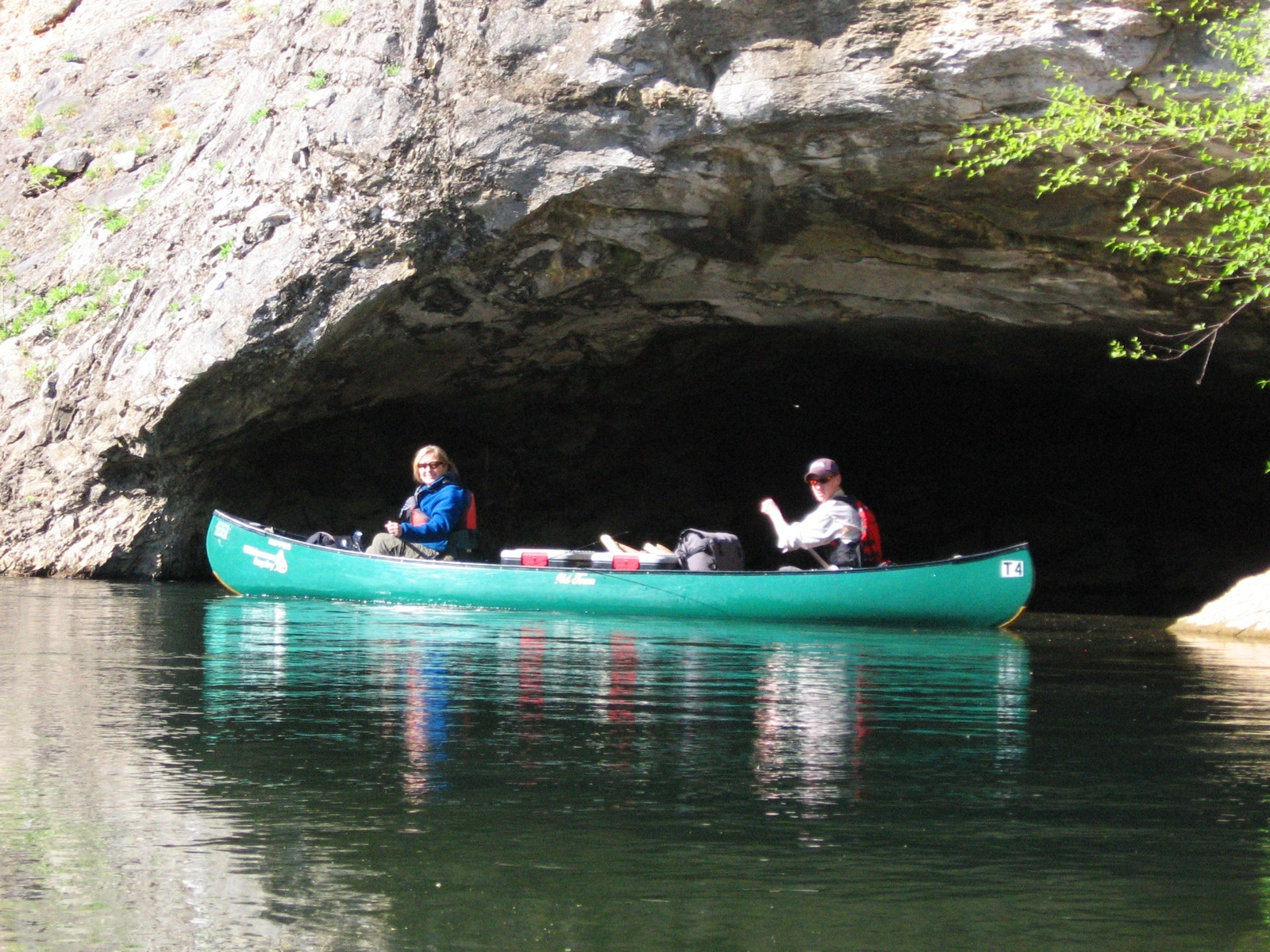 Two canoeists in a green tandem canoe paddle past a river cave on their way to Hasty campsite in the Ozarks.