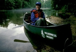 A smiling participant sits in a canoe while it's beached for a lunch break along the Buffalo River.