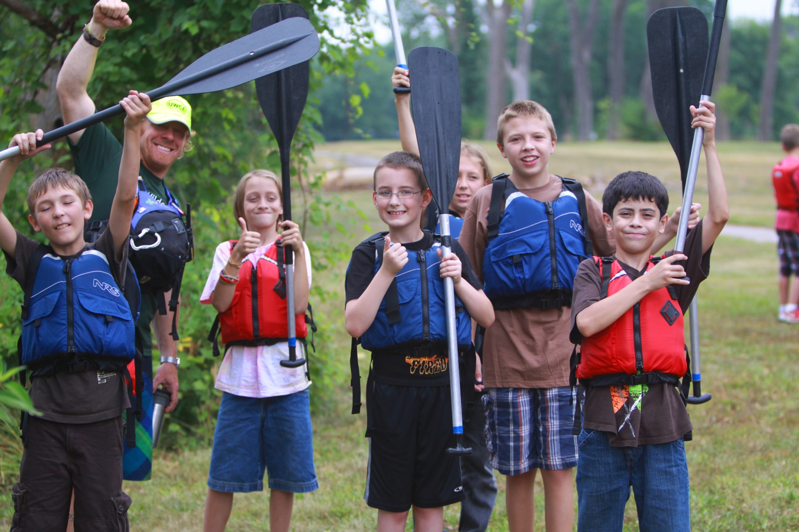 young participants hold their paddles and thumbs up while standing on land