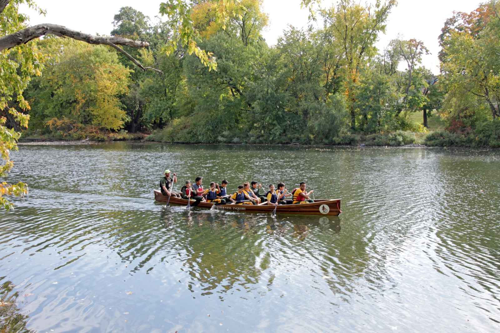 a voyageur canoe paddles along a wide river in late summer