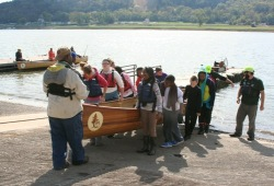 staff and participants work together to move a Voyageur canoe out of the water