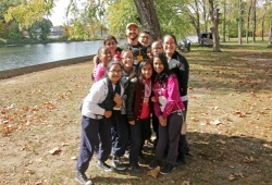 a group photo of a staff member and 10 participants in the fall by a river