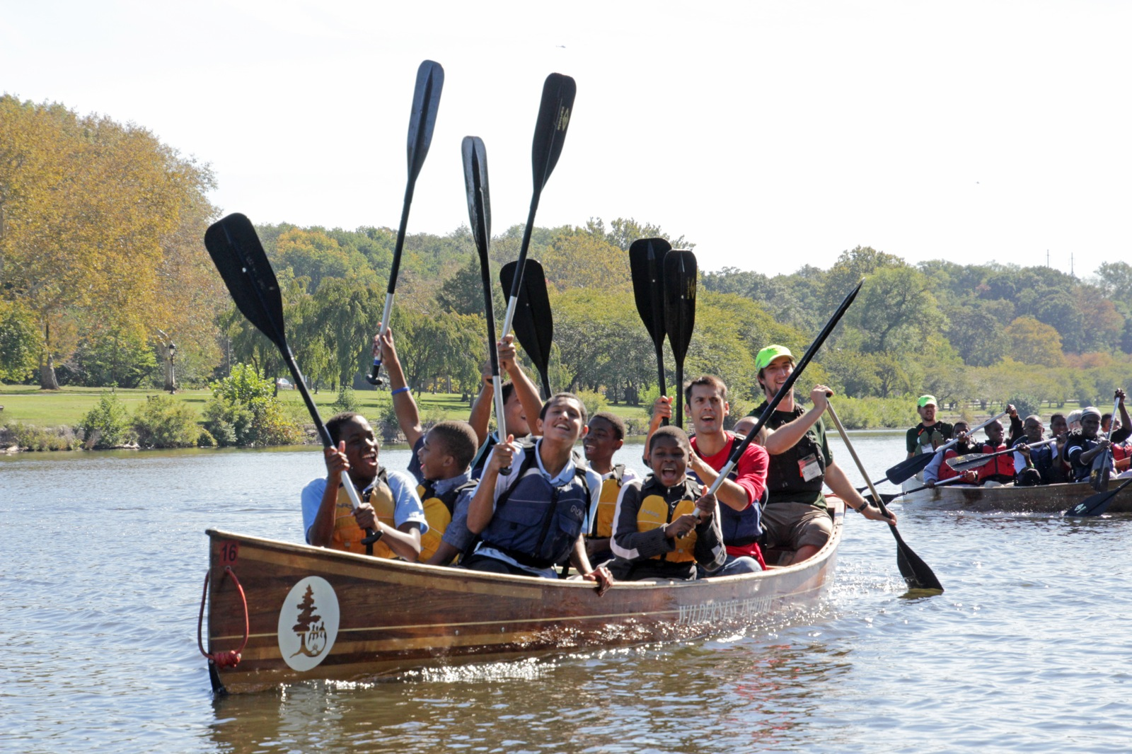 a group of participants hold their paddles above their heads as they smile for the camera in the Voyageur canoe