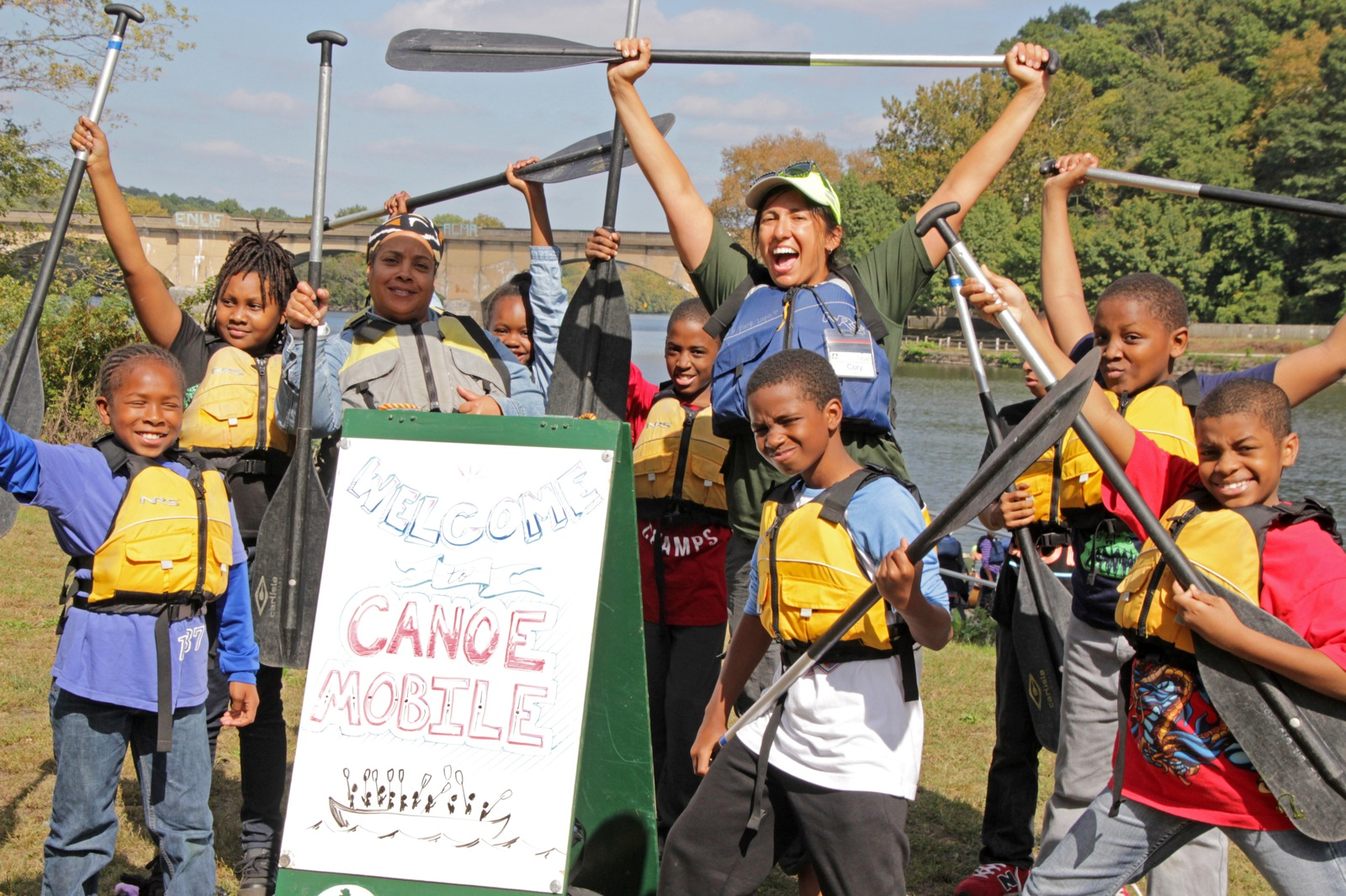 8 participants and a staff member pose with their paddles next to a Canoemobile sign